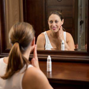 Creme gegen Altersflecken AnwendungFrau schaut in Spiegel und reibt sich eine Creme ins Gesicht